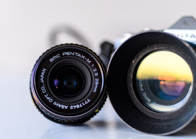 SMC Pentax lenses and Pentax Me body in background.