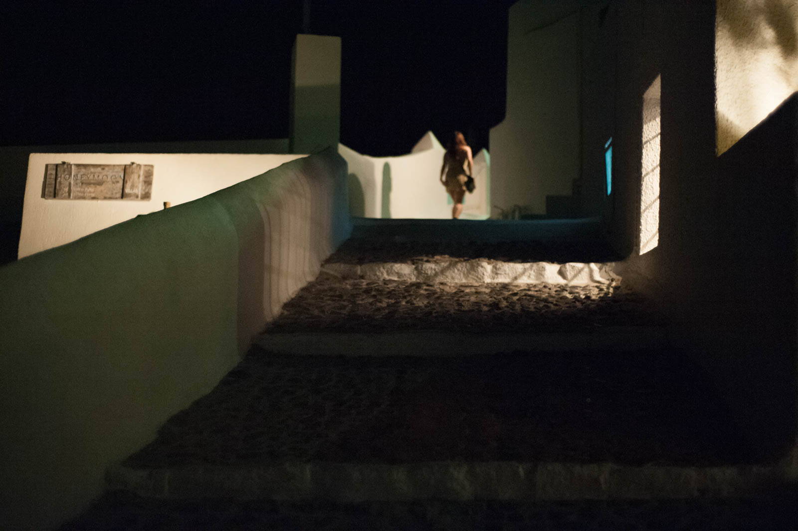 Woman walking at top of stairs in the dark. Imerovigli, Santorini.